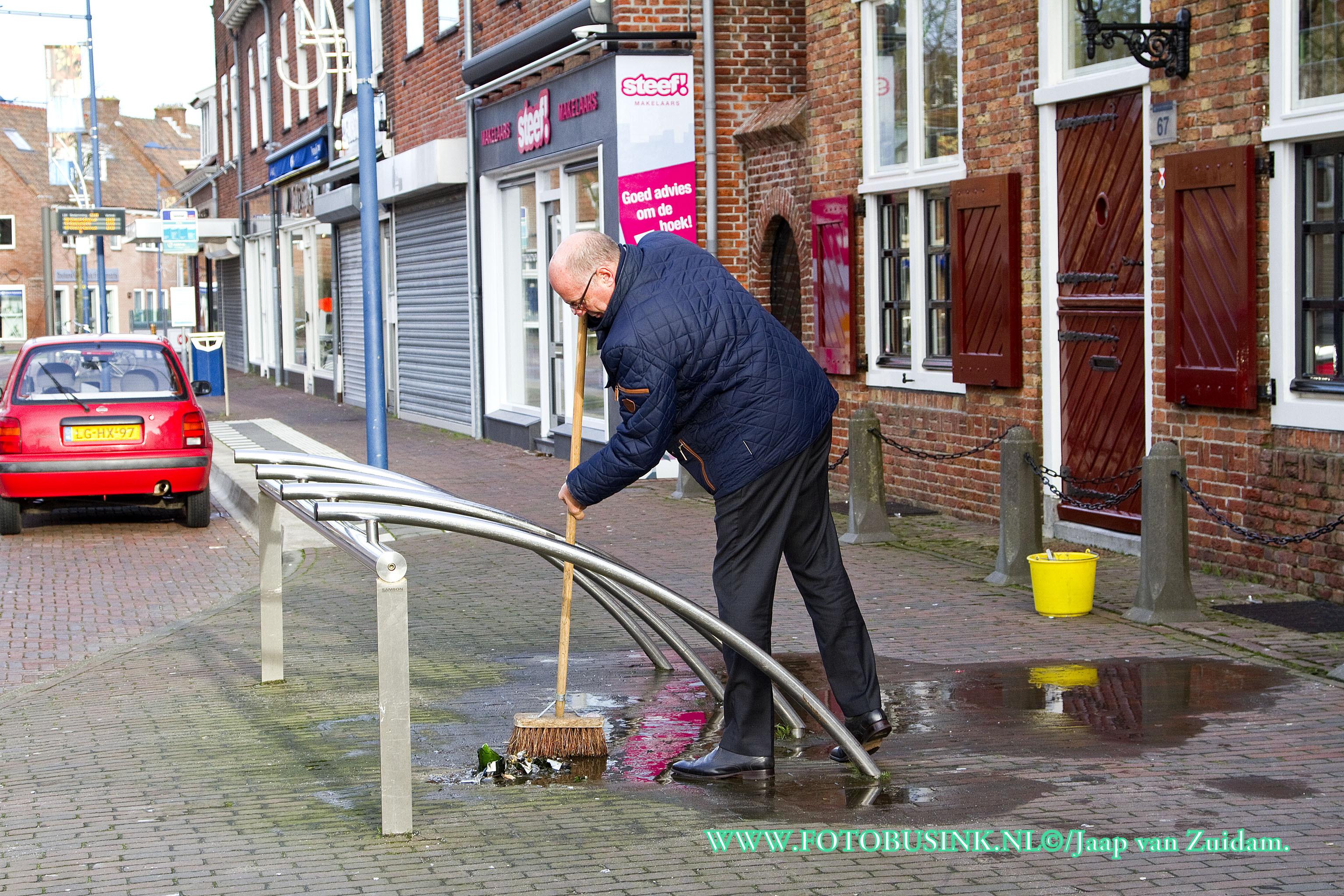 Winkelier veegt op nieuwjaarsdag de straat schoon.