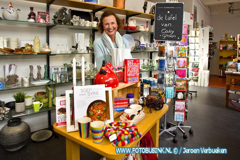 Caty Groen dekt de wereldtafel in de wereldwinkel in Dordrecht.
