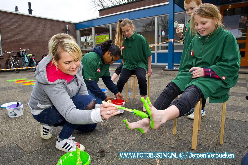 Leerlingen hard aan het werk op hun school De Regenboog in Dordrecht met vrijwilligers van Nl-doet. + video