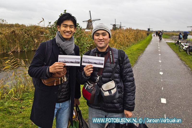 Molenbewoners Kinderdijk delen ansichtkaarten uit aan toeristen tegen overtoerisme.