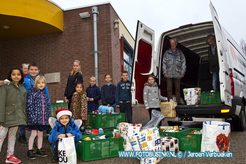Leerlingen van basisschool De Satelliet uit Dordrecht geven bus vol voedsel aan de voedselbank.