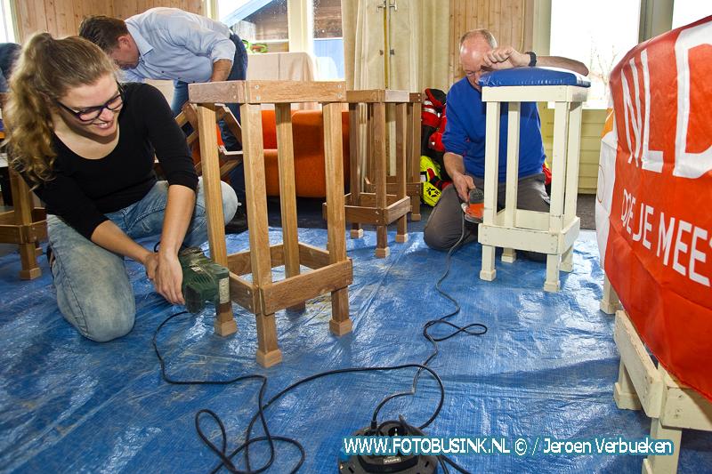 Vrijwilligers NL-doet helpen met klussen bij de reddingsbrigade in Hardinxveld-Giessendam.