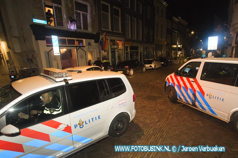 Man met glas gestoken aan de Voorstraat in Dordrecht.