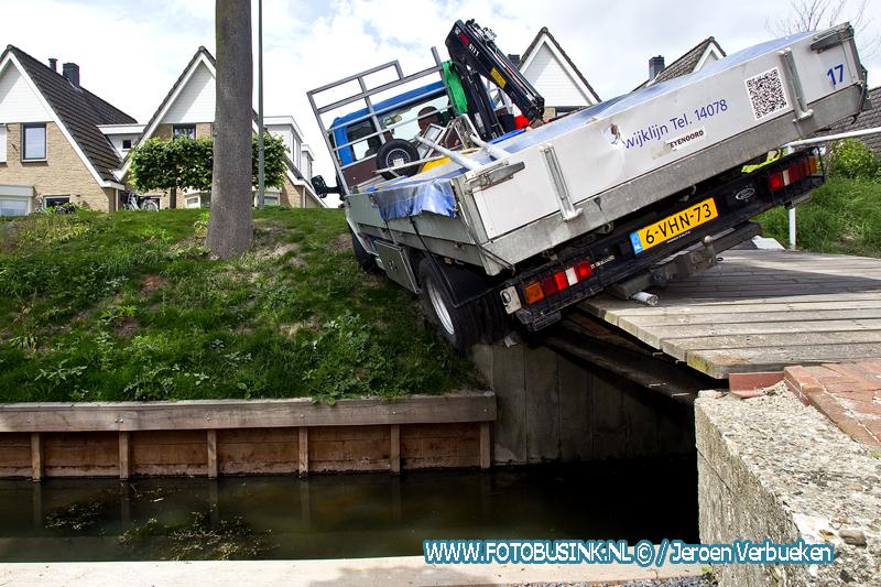 Gemeentewagen belandt beneden aan de Vissersdijk bijna in het water.