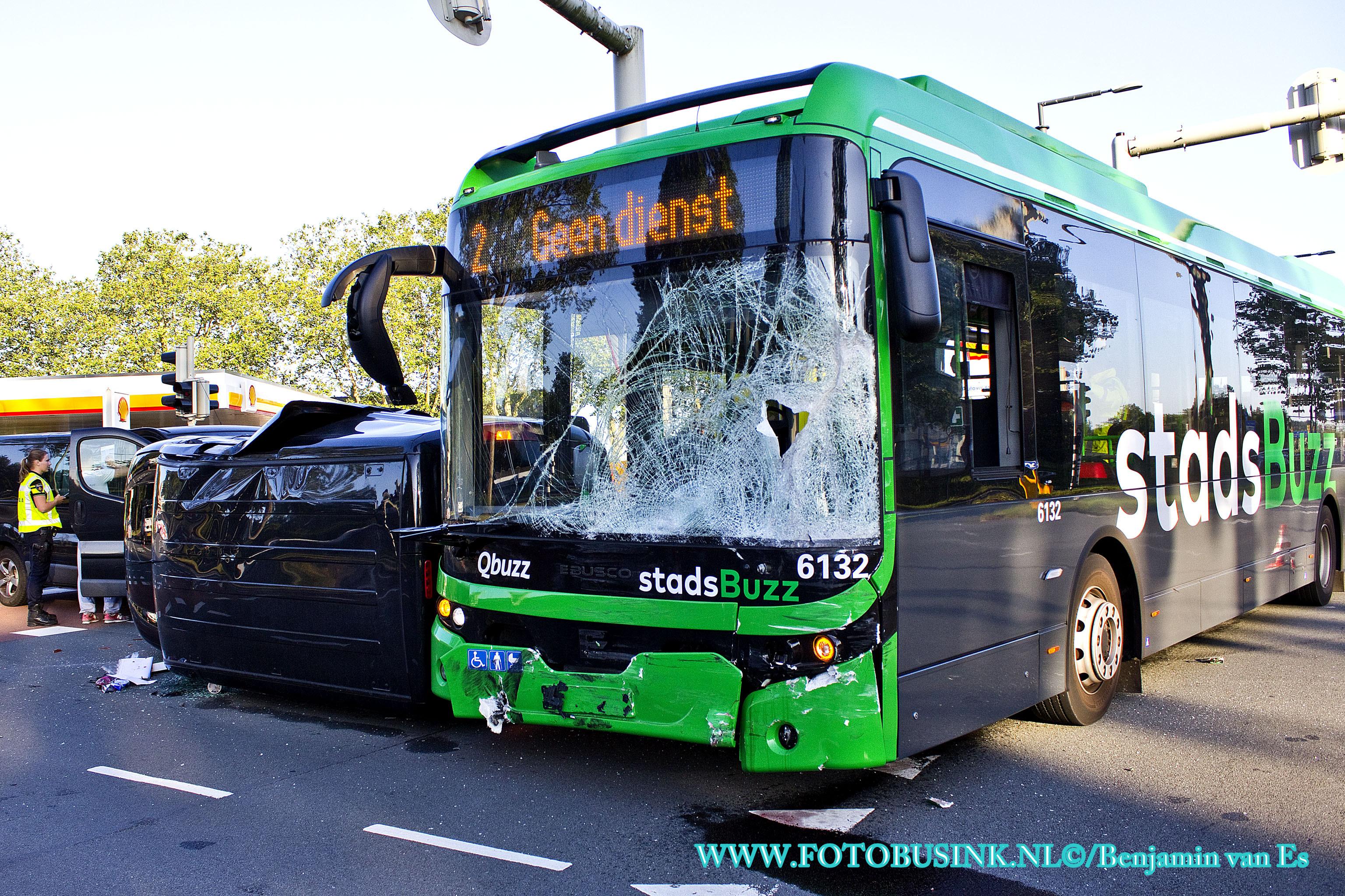 Busje op zijn kant na aanrijding met stadsbus.