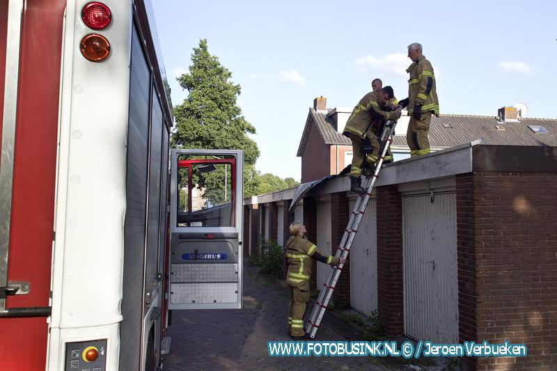 Dakbedekking laat los door harde wind van garage's aan de Schipbeekstraat in Dordrecht.