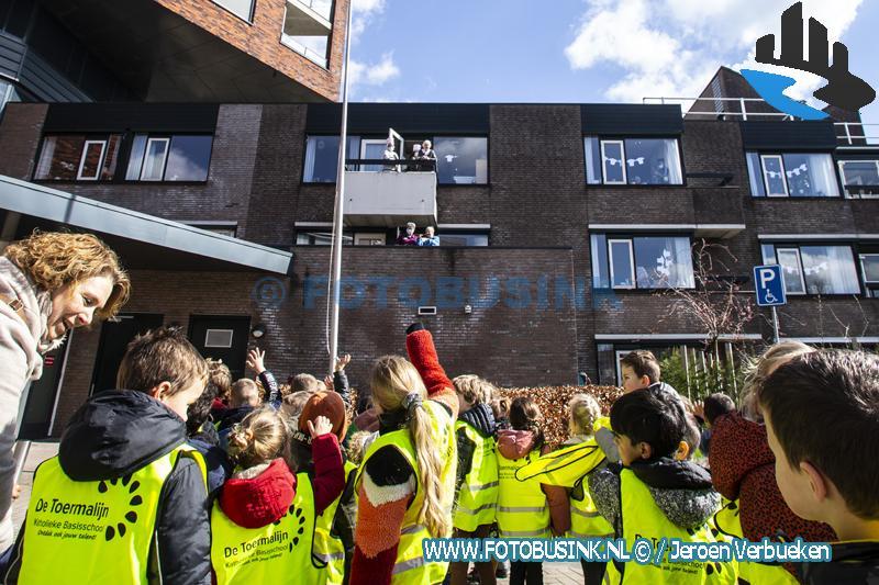 Basisschoolkinderen zwaaien naar de ouderen in de Lichtkring