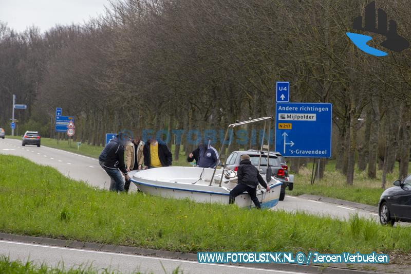 Omstanders helpen boot van de weg te halen aan de N217 in 's-Gravendeel