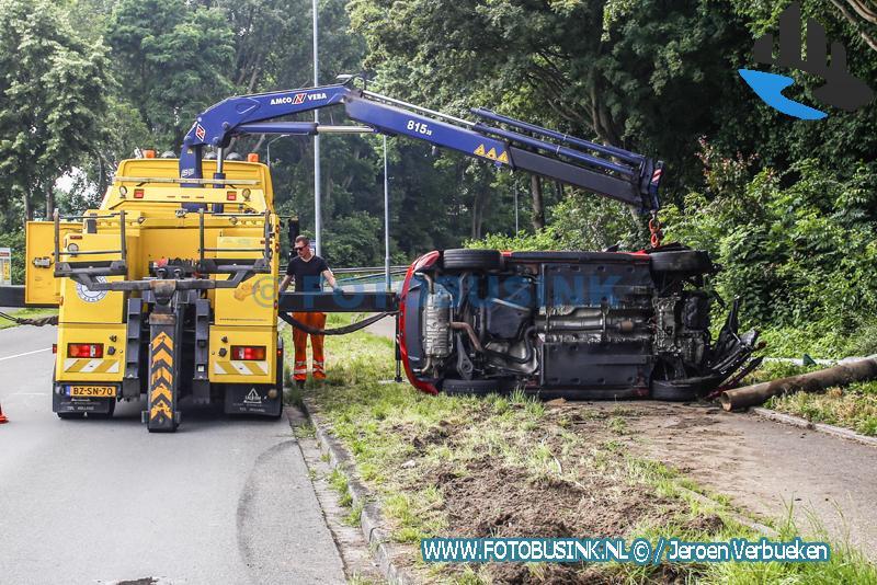Auto op zijn kant op de Brugweg in Dordrecht